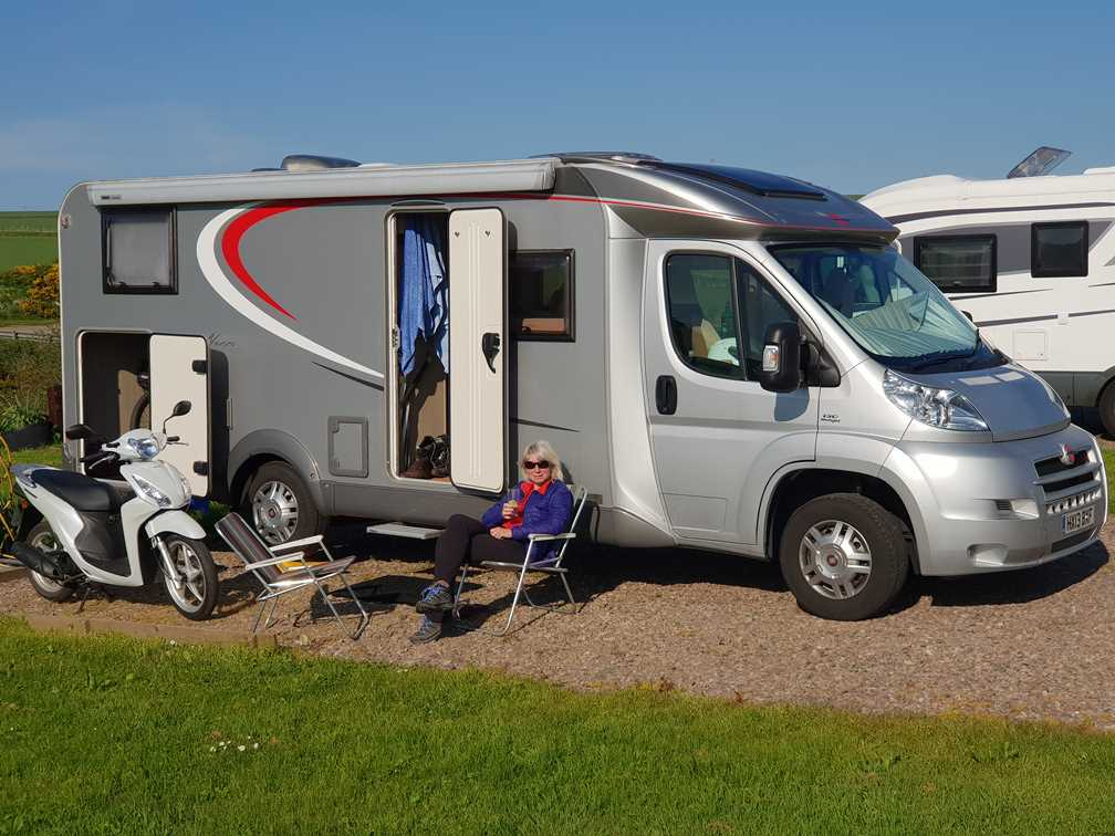 Sitting outside the motorhome at Gamrie Bay on our Scotland road trip