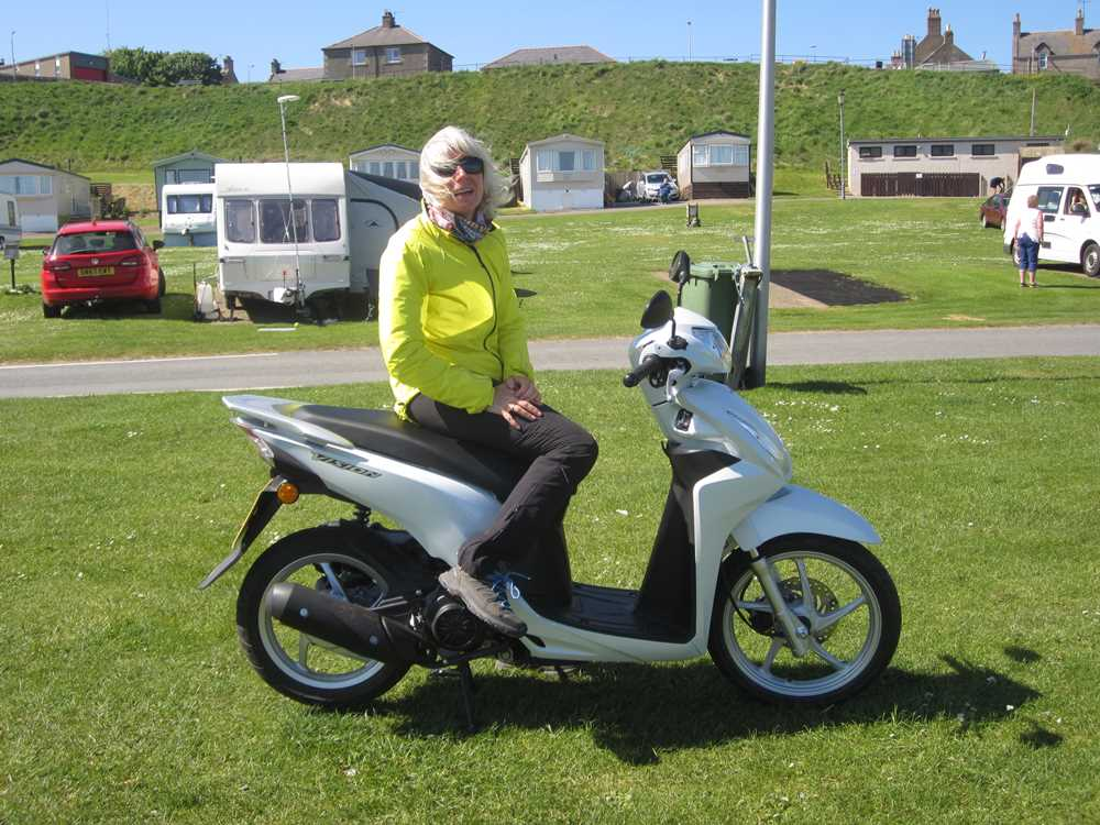 Me with our tiny scooter on a Scottish road trip