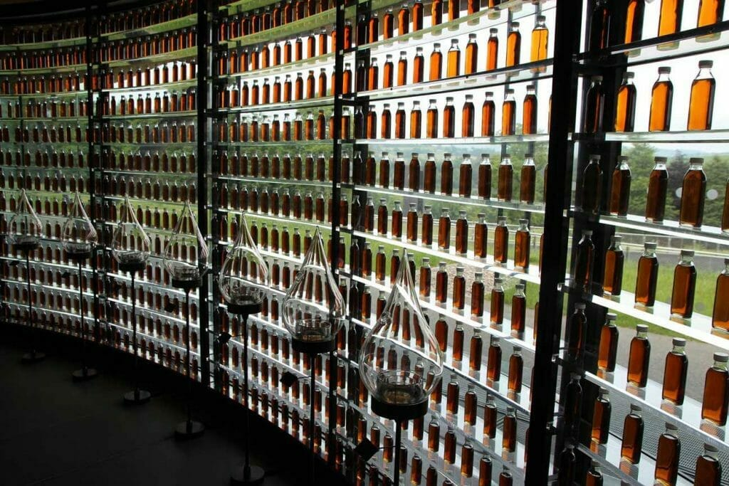 A wall of bottles with all the colours of whisky
