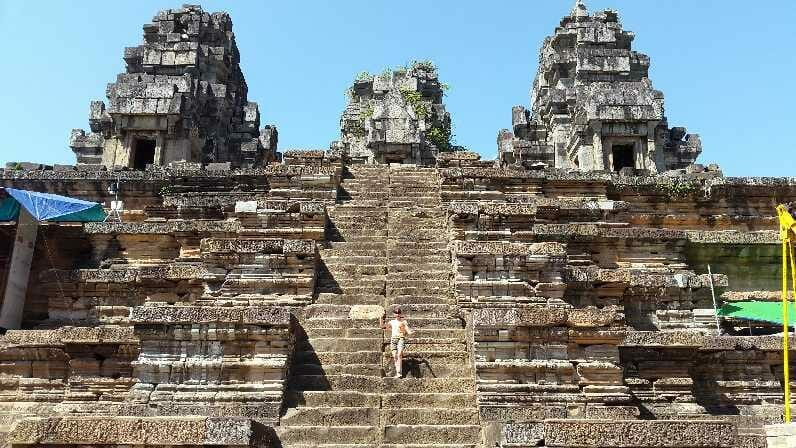 On steps of temple on cycle tour of Cambodia