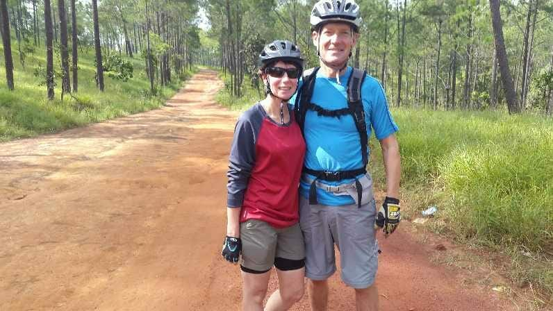 Jane and Peter on track in forest whilst cycling in Cambodia