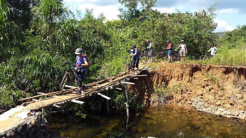 Crossing rickety bridge with bikes on Cambodia by bike trip