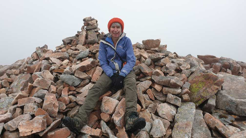 Jane sitting on cairn on top of Meall Cuanail